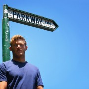 Founder of the band Parkway Drive, Ben Gordon, in front of the sign at the entrance to the street. Gordon has joined the community opposition to the planned development at Ewingsdale.