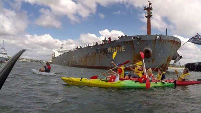 Protesters paddle in front of a coal ship. Image from world.350.org/pacificwarriors/newcastle-flotilla-live-blog