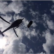 A police helicopter winches cannabis plants during raids. (supplied)