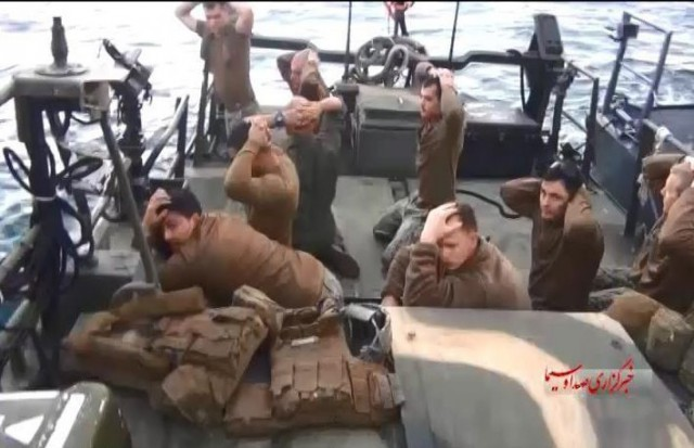 A handout TV grab made available by the official website of Iranian state television (IRIB) on 13 January 2016 shows American military personnel on their boat after they were captured by the Iranian Revolutionary Guard Corps (IRGC), at an undisclosed location in Iran, 12 January 2016.