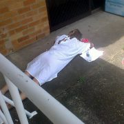 A woman lying on concrete outside Ballina Hospital on New Year's Day, when the hospital waiting room was full. Photo Maralyn Sweeney