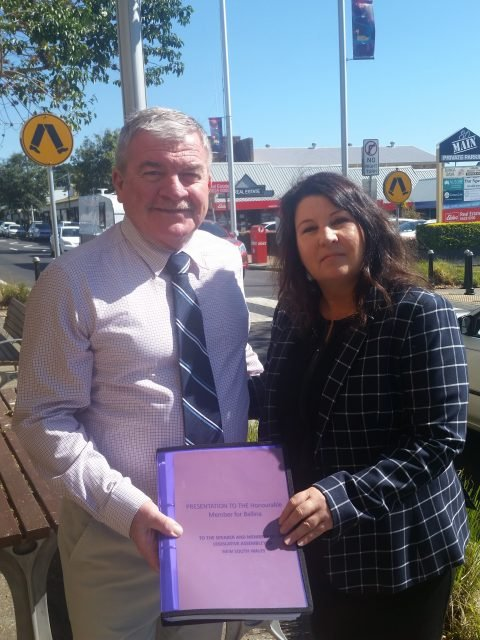 amara Smith receives the Alstonville community petition from Rod Clavan (left) outside the Alstonville Newsagency. Photo supplied