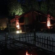 Statues look over the fire at night in New Zealand at a hangi